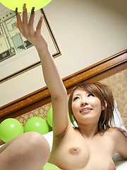 Lovely Asian model is showing off her big tits and smiling