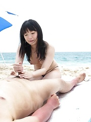 Hina Maeda Asian licks balls and rubs tool with feet on beach
