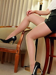 Kurumi Kisaragi Asian shows sexy legs in short skirt on furniture